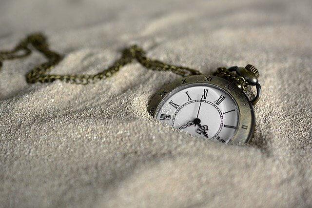 砂に埋もれる懐中時計